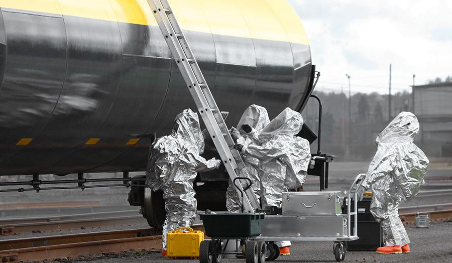CBRN Detection in One Compact Package. Hazmat team approaching a freight train.